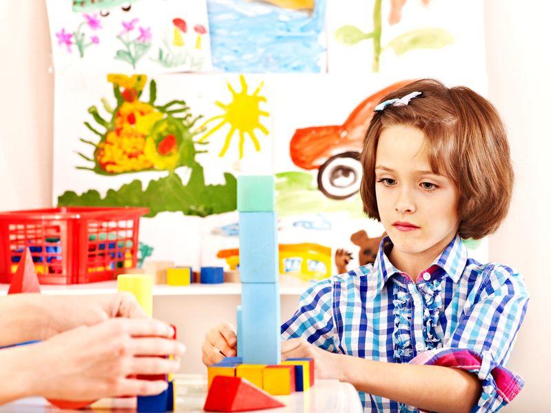 Beautiful Kid playing blocks game at home during lockdown