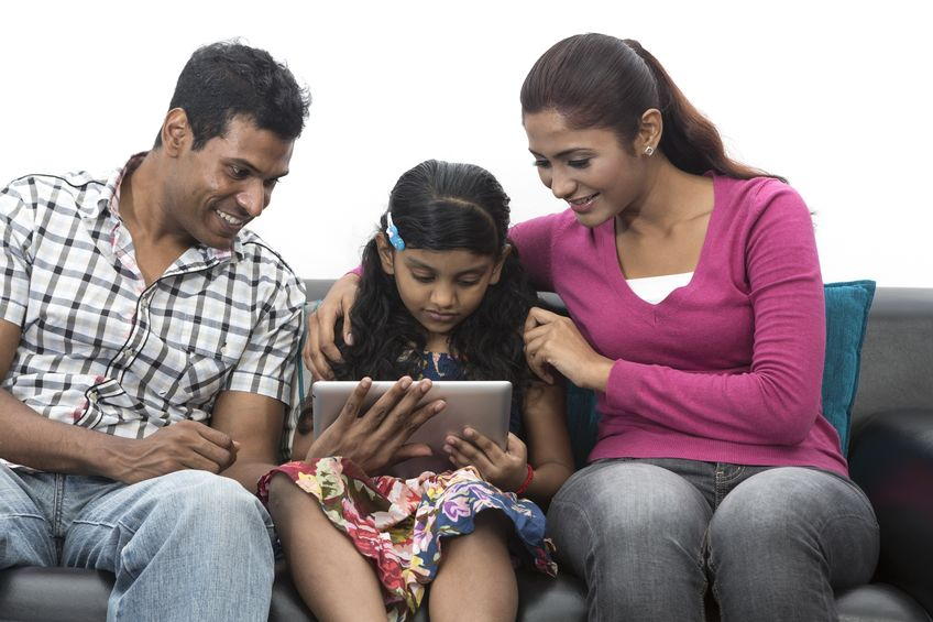 Father Mother helping daughter to learn mobile apps
