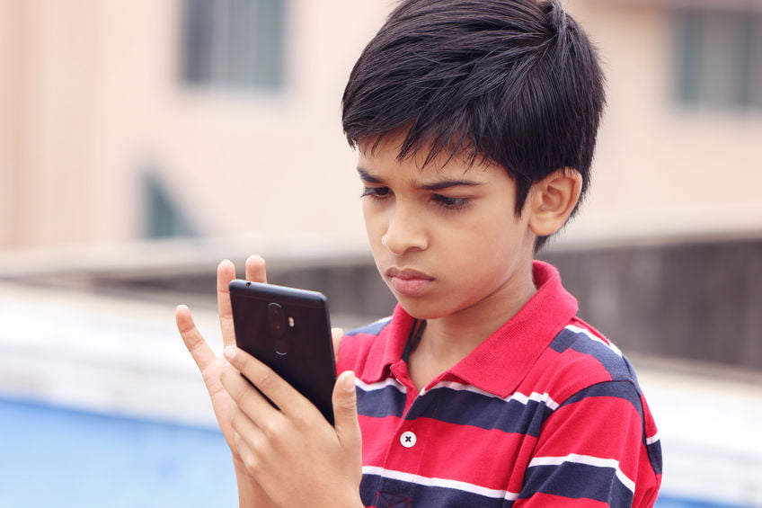 Addicted Indian Child playing games in phone